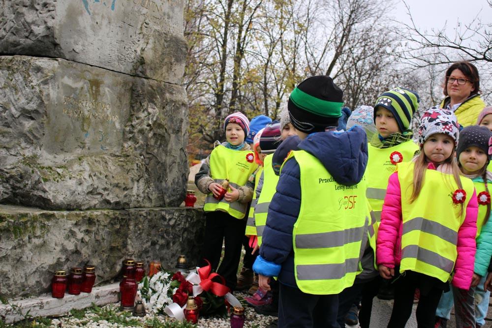 Dzieci składające kwiaty pod pomnikiem poległych za wolność w parku im. Szuberta