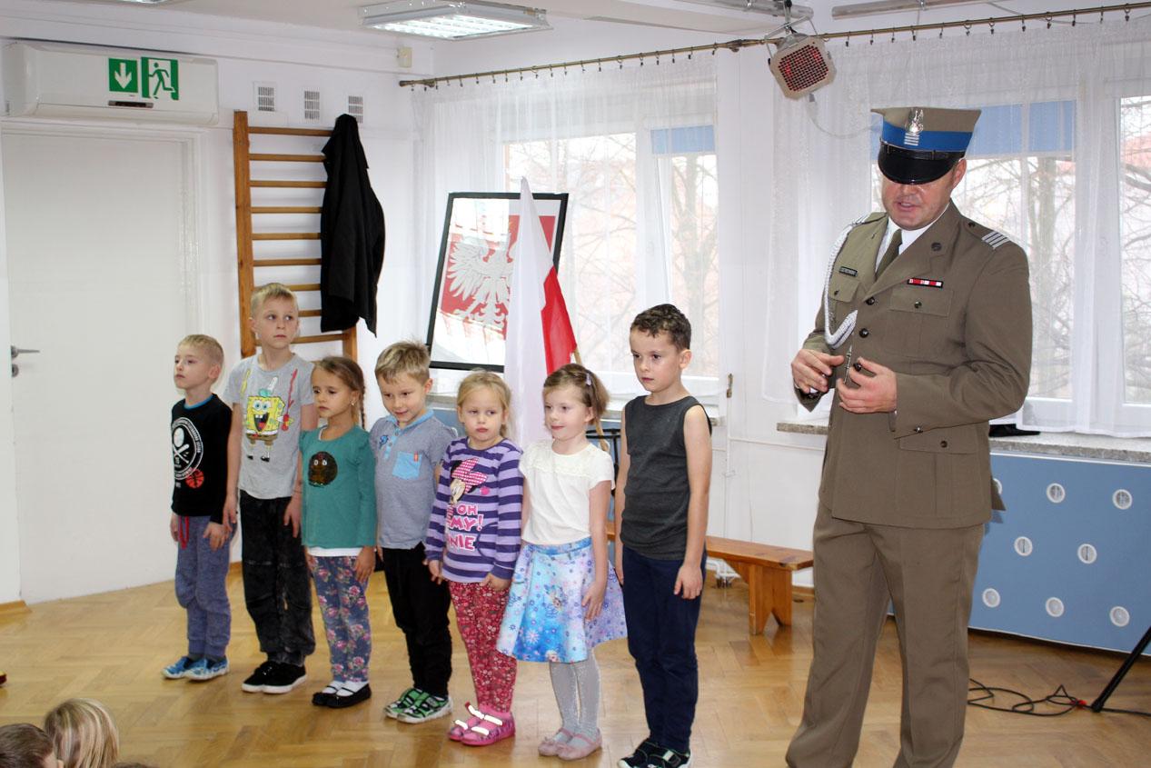 Żołnierz czyta dzieciom w ramach projektu Mały Miś w świecie wielkiej literatury.